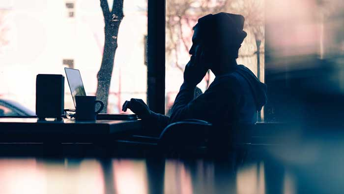 Student sitting in a coffeehouse attending an online lecture