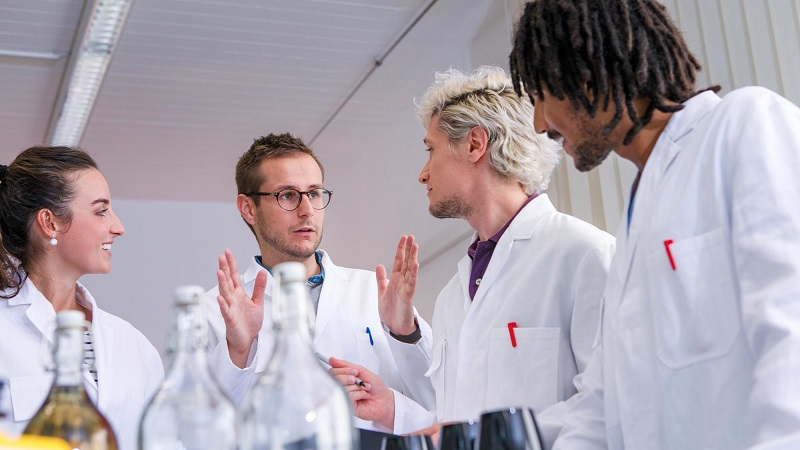 Lecturer explaining something to three students in a laboratory