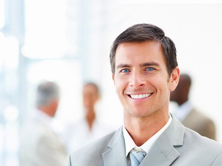 Young smiling business man standing in front of a group in the background, blurred, in a bright surrounding